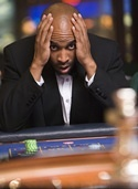 Man losing at roulette table in casino